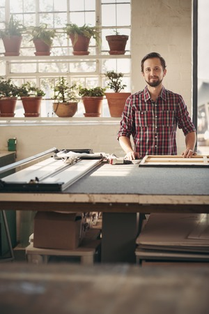 picture framing: Young male designer entrepreneur standing proudly in his studio at his workbench smiling with beautiful light coming in through the window
