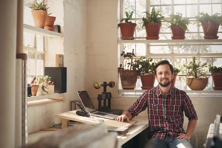 아름다운 자연의 빛과 많은 식물이 자신의 스튜디오에서 자신의 사무실 공간에서 편안하게 앉아 젊은 남성 디자이너