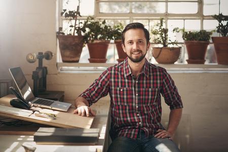 Jonge mannelijke ondernemer zitten in het kantoor van zijn design studio kijkt vol vertrouwen naar de camera Stockfoto