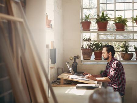 Jonge mannelijke ontwerper zitten en werken op zijn laptop in een kantoorruimte in zijn creatieve design studio