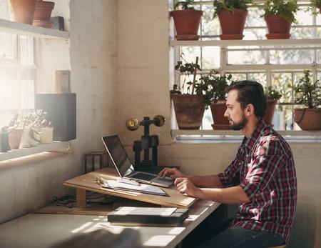 Jonge ontwerper te typen op zijn laptop, terwijl de vergadering op een creatieve ruimte die hij gebruikt als zijn kantoor in zijn atelier