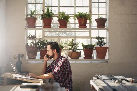 Młody projektant przedsiębiorca patrząc na jego laptopie podczas rozmowy przez telefon w jego miejscu pracy w studio