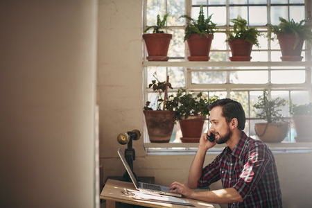 business man phone: Designer looking positive while talking on his phone at his desk in his studio