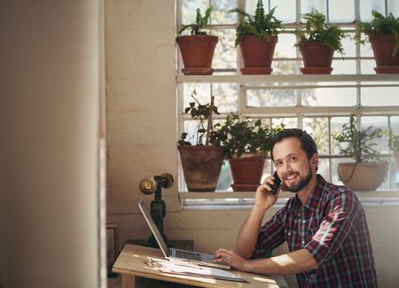 Male designer working at his studio desk while talking on the phone and looking up to smile at the camera Stok Fotoğraf
