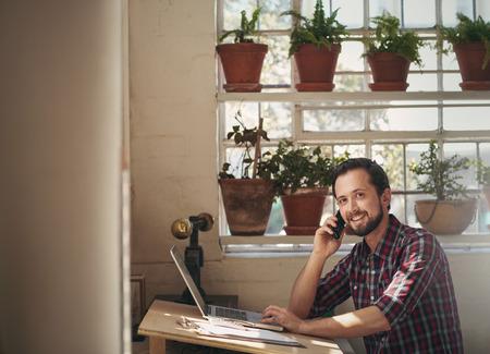 Man ontwerper werken in zijn studio bureau tijdens het praten aan de telefoon en het opzoeken van te glimlachen op de camera
