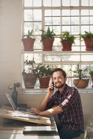 Lachende ondernemer zitten aan de balie van zijn atelier kantoor en kijken aangenaam naar de camera terwijl u luistert naar zijn mobiele telefoon