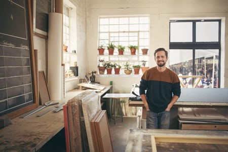 adult male: Young male craftsman standing with his hands in his pockets, in his workshop and smiling at the camera in a way that is both confident and comfortable