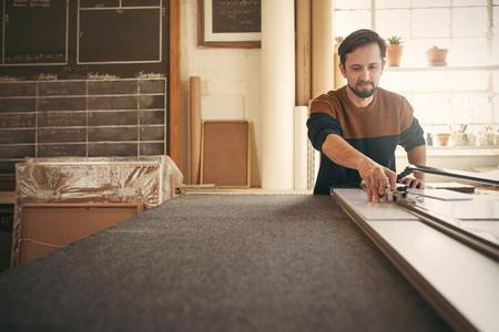 Jonge mannelijke ontwerper werken met de concentratie en het gebruik van een hulpmiddel bij zijn werkbank in zijn studio