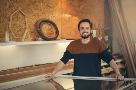 framer: Craftsman standing positively in his design studio looking proud and confident