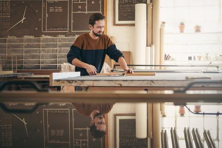 Jonge professionele lijstenmaker met behulp van speciale gereedschappen in zijn atelier atelier, terwijl zich te concentreren op vakmanschap