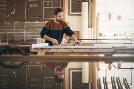 framer: Young professional framer using specialised tools in his workshop studio while concentrating on craftsmanship Stock Photo