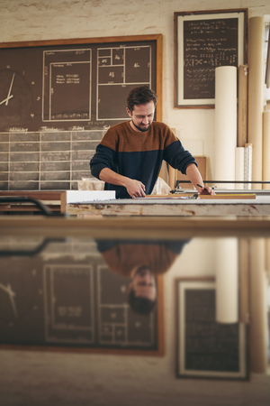 framer: Skilled carpenter working with concentration on a project in his woodworking studio