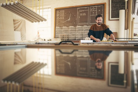 framer: Professional craftsman working with skill and concentration in his naturally lit studio