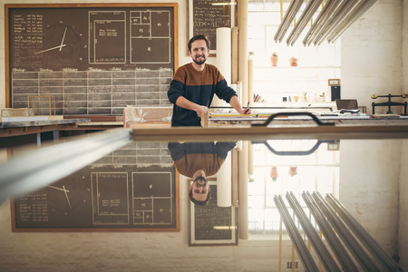 picture framing: Portrait of a positive and professional framer at work in his studio, with tools on his workbench and looking up at the camera with a smile
