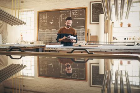 Jonge ontwerper in zijn atelier atelier controleren van voorraad en bestellingen met een klembord en pen Stockfoto