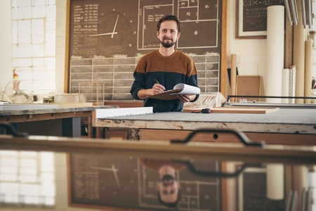 framer: Portrait of a professional craftsman smiling at the camera while working in his studio and using a clipboard and pen to check stock and orders Stock Photo
