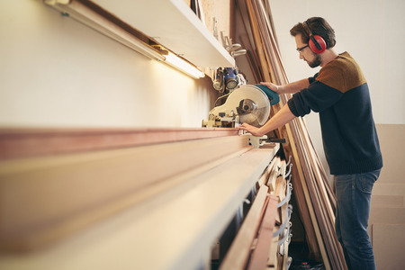 business: Professionell hantverkare i arbete i en inramning verkstad med hjälp av en såg verktyg för att arbeta med trä