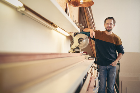 framer: Young professional framer posing alongside a specialised tool in his workshop looking proud and smiling happily