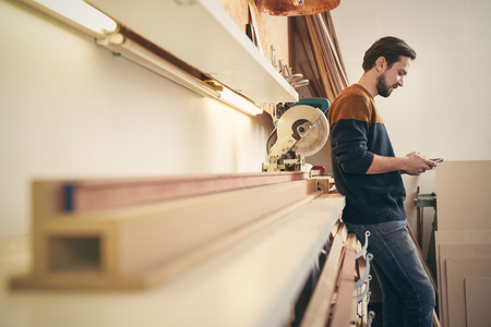 business lifestyle: Craftsman leaning against a work area in his workshop using his cell phone to send a message Stock Photo