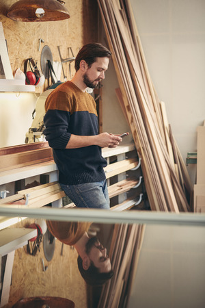 picture framing: Designer craftsman looking casual and using his phone to send a message while standing in his studio workshop
