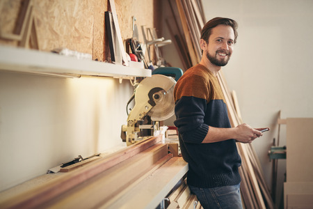 framer: Young man using his phone and looking up with a smile while standing casually in his carpentry workshop Stock Photo