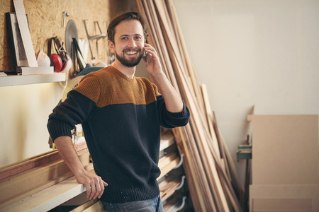 picture framing: Portrait of a young man smiling while talking on his phone and standing casually in his woodworking workshop