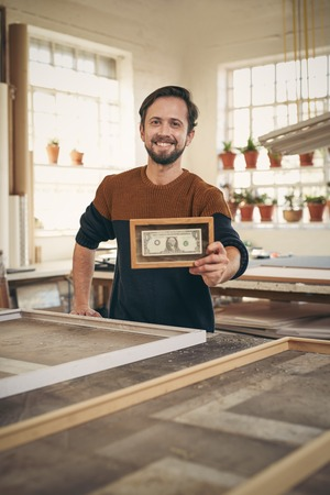 framer: Young craftsman holding up a bank note that has been framed while standing proudly in his workshop