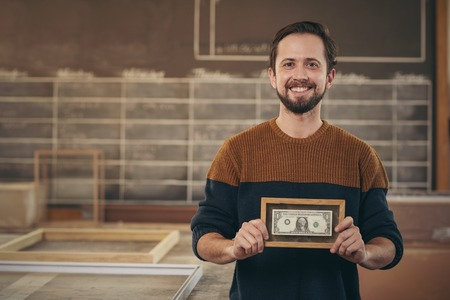 business money: Smiling craftsman entrepreneur standing proudly in his workshop and displaying a bank note that has been carefully framed