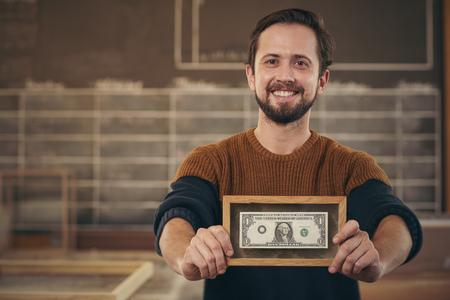 Sorridente imprenditore in piedi con orgoglio nel suo laboratorio e mostrando una banconota che è stato incorniciato