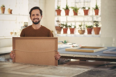 confidently: Portrait of a young male professional framer holding a newly framed work while smiling confidently at the camera in his studio wrokshop
