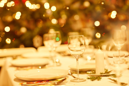 Closeup shot of a table set with glassware, plates and cutlery for a Christmas dinner