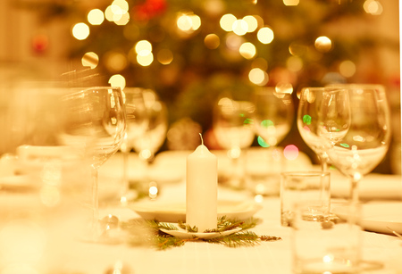 table linen: Table prepared for a family celebration dinner with a tradtional Christmas tree in the background