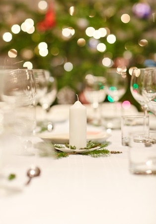 christmas decor: Closeup shot of a table set with glassware, plates and cutlery for a Christmas dinner