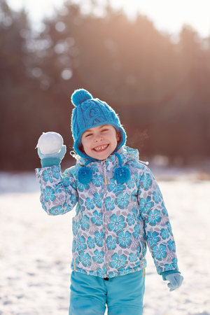 cheeky: Cute little girl holding up a snowball with a cheeky smile outdoors on a winters day Stock Photo