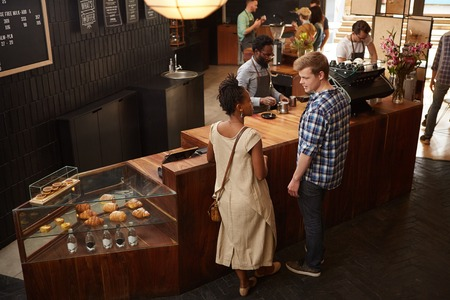 high angle view: High angle view of an African woman and caucasian man who are friends, chatting at the modern wooden counter Stock Photo