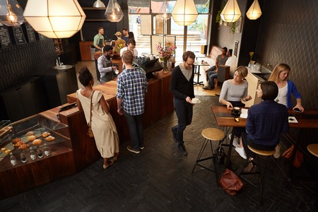 high angle view: High angle view of a busy popular coffee shop with modern styling in which there are customers Stock Photo