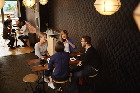 Four young adults sitting in a group together having a friendly meeting on a break in a modern and popular coffee shop