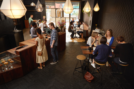 high angle shot: High angle shot of a modern coffee shop in which there are baristas making coffees behind the counter