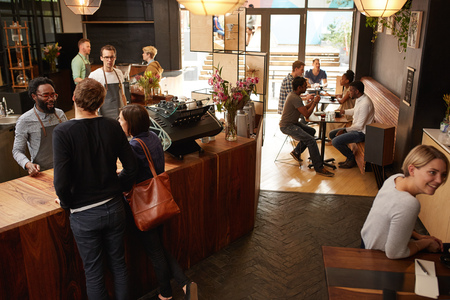 High angle shot of a couple ordering at a wooden counter in a modern coffee shop with a hipster style