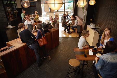 amigas conversando: Sonriendo barista detrás del mostrador de madera de una cafetería moderna ocupada que tiene una conversación amistosa con algunos clientes Foto de archivo