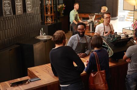 Przystojny afroamerykańskiej mężczyzna pracuje jako profesjonalny barista w nowoczesnej kawiarni Zdjęcie Seryjne