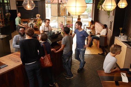 Klanten wordt geholpen door professionele barista's, terwijl die zich op een houten teller plaatsen hun bestellingen Stockfoto