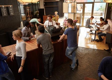 Dos propietarios de pequeñas empresas que trabajan detrás del mostrador de su tienda de café ocupada con una decoración moderna Foto de archivo