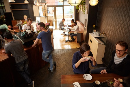 high angle view: High angle view of a coffee shop with modern decor and some customers standing at the counter