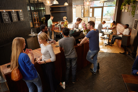 Women and men waiting at a modern coffee shop wooden counter talking and waiting for their coffee orders photo