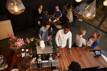 モダンなコーヒー ショップの木製のカウンターでの注文顧客を笑顔のオーバー ヘッド ショット