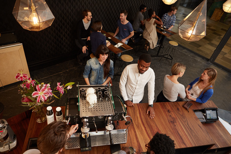 Overhead schot van lachende klanten plaatsen hun bestelling op de houten balie van een moderne koffieshop
