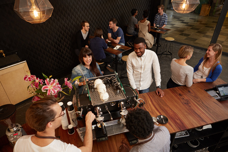 baristas: Topview image of a multi-racial couple sharing a laugh with the baristas behind the counter