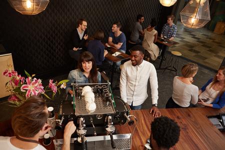 Hoge hoek shot van een mooie vrouw het bestellen van een koffie uit een barista over een espresso-apparaat in een drukke koffieshop