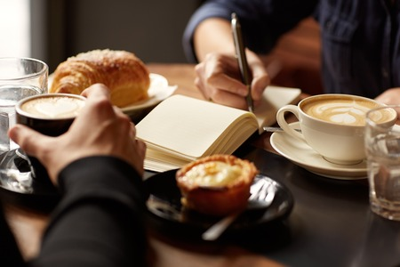 coffee meeting: Cropped image of two peoples hands at a table with coffees and pastry snacks Stock Photo
